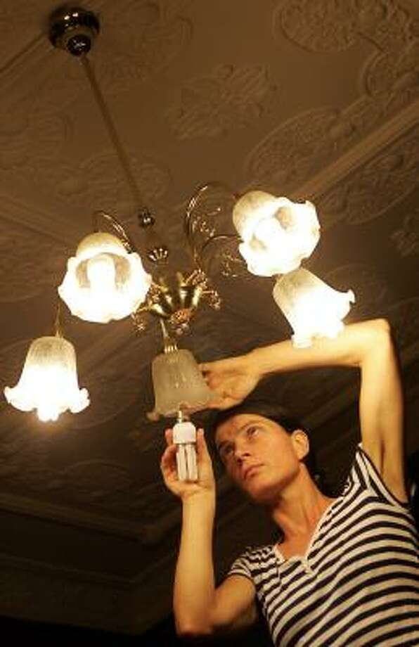 Heidrun Strohmeyer installs a free, government-supplied fuel-efficient compact fluorescent bulb in her 100-year-old home in Sydney on Tuesday. Australia is banning incandescent light bulbs by 2010. Photo: TORSTEN BLACKWOOD, AFP/GETTY IMAGES