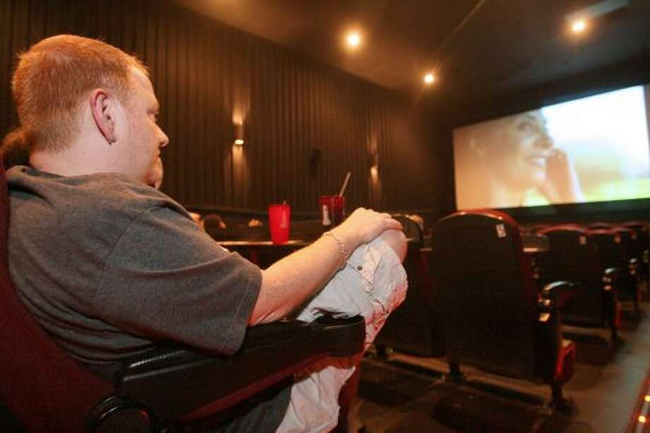 Steve Lease catches the end of Prison Break while waiting for 24 to begin at the Alamo Drafthouse Mason Park in Katy. Photo: BILL OLIVE, FOR THE CHRONICLE