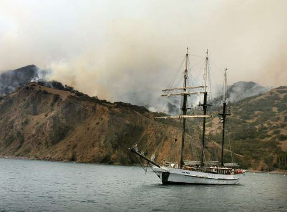Smoke rises in the Catalina Island hills from a wildfire burning Friday in Avalon, Calif. The fire has been 35 percent contained. The city's cobblestone streets, landmark casino and hotels were mostly spared. Photo: J. EMILIO FLORES, GETTY IMAGES