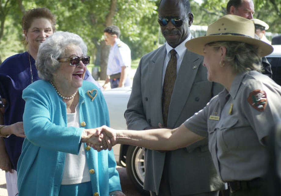 Former first lady Lady Bird Johnson, 89, left, greets a park ranger as she arrives for the annual wreath-laying ceremony at the cemetery where her husband was buried after his death in 1973,  in Stonewall, Texas, in this 2002 file photo. Photo: ERIC GAY, AP