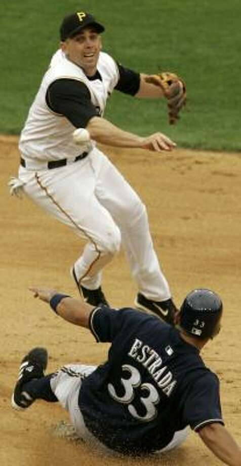 Jack Wilson helps the Pirates escape a first-and-third jam in the sixth inning by completing a double play, despite the slide by Johnny Estrada. Photo: GENE J. PUSKAR, AP
