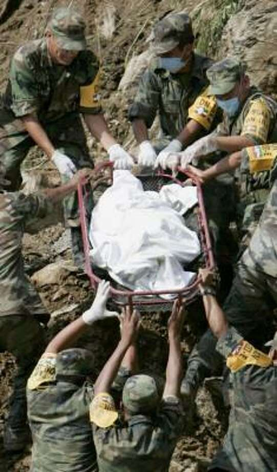 Soldiers transport the body of a victim in San Miguel Eloxochitlan, Mexico, Thursday where a landslide on a rural road crushed a bus carrying an estimated 40 people. Photo: EDUARDO VERDUGO, AP