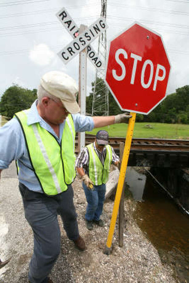 County workers Randy Parisher, left, and Leo Ortega, put up a stop sign at the railroad track on East Archer Road, outside Baytown, where four teens died in a SUV crash with a train. Photo: Steve Campbell, Chronicle