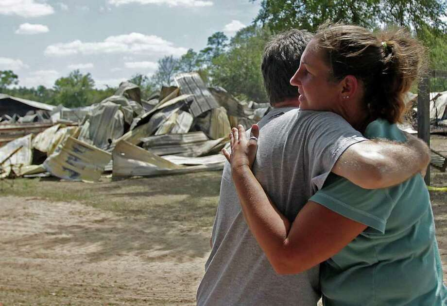 With the remains of a burnt-down stable behind them, Jennifer Goslin, owner of the Goslin Nix Training Center gets a hug from neighbor, Bryan Hughes, after an early morning stable fire at the training center at the corner of FM 1488 and Superior Rd. left 13 Arabian and Arabian-mixed horses dead Tuesday, Aug. 9, 2011, in Magnolia.  Fourteen horses were able to escape or were released from their stables, some suffering from burns and smoke inhalation. One horse is currently unaccounted for. Fourteen horses were able to escape or were released from their stables, some suffering from burns and smoke inhalation. One horse is currently unaccounted for. ( Johnny Hanson / Houston Chronicle ) Photo: Johnny Hanson, Staff / © 2011 Houston Chronicle
