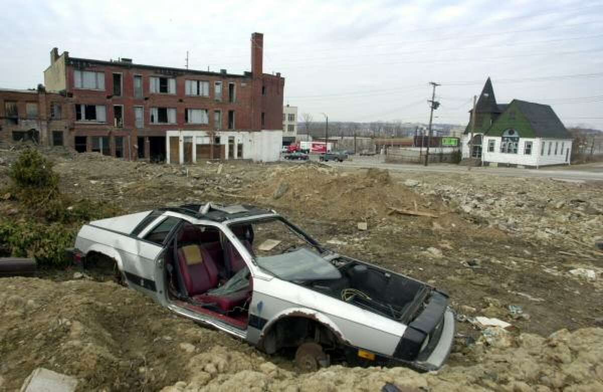 An abandoned car sits near an abandoned building across the river from downtown Youngstown, Ohio, in 2001. The city saw its population plunge from 140,000 in the early 1970s to just over 80,000 today.