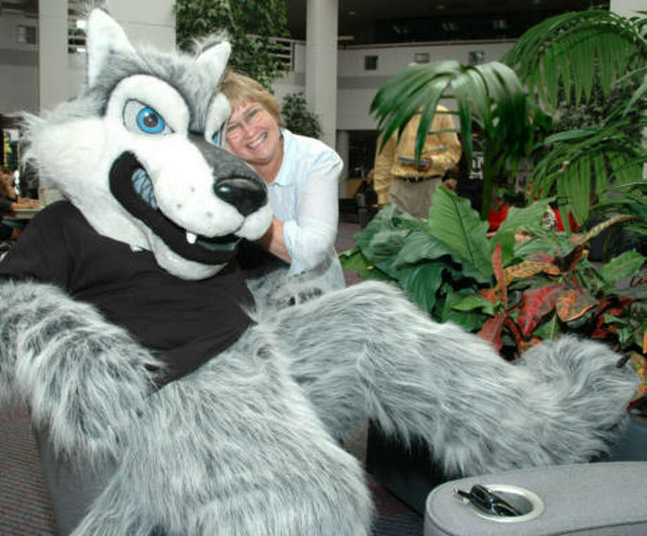 Suzann Staats, a graphic designer, hangs out with Tomball College's new mascot, Trevor the Timberwolf. Photo: Janice Smith, For The Chronicle