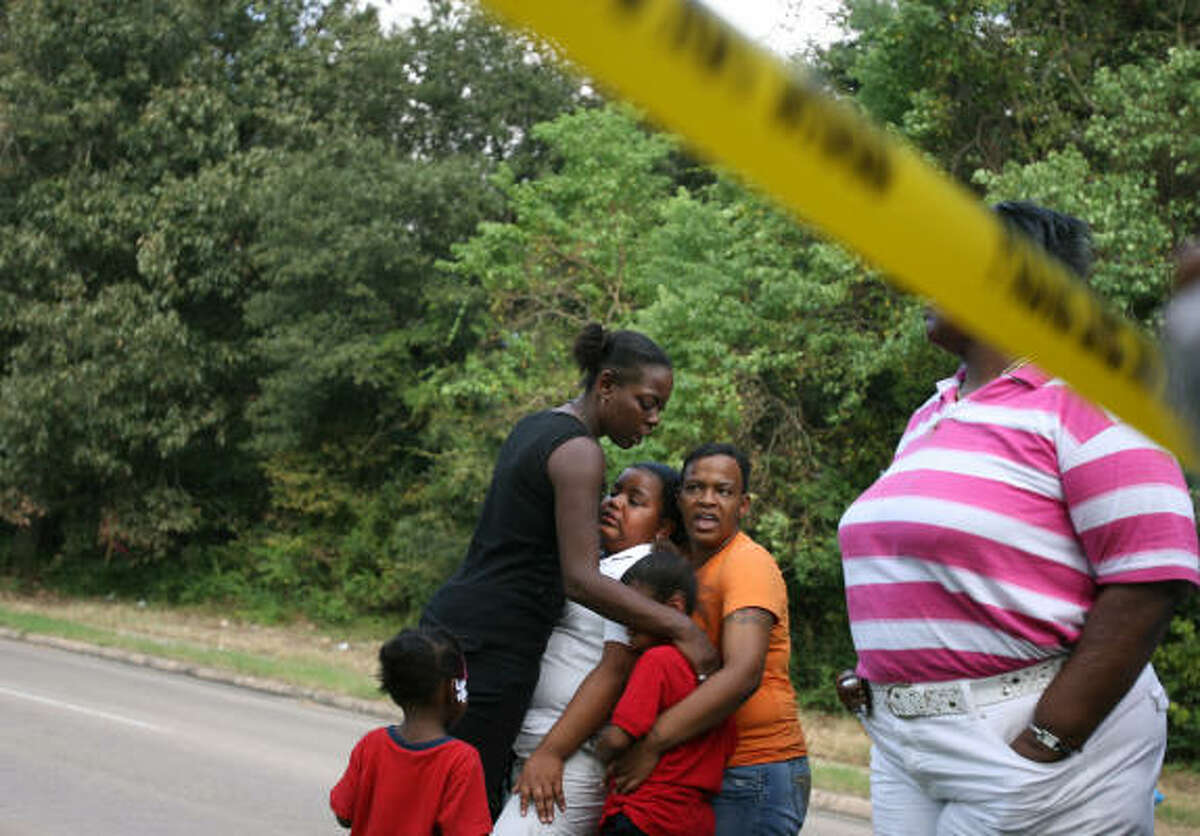 The family of 29-year-old Raymond Smith gather at the scene where he was shot and killed by a Houston police officer in the 6000 block of East T.C. Jester.