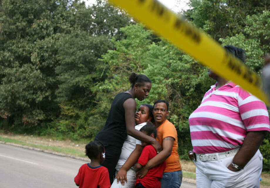 The family of 29-year-old Raymond Smith gather at the scene where he was shot and killed by a Houston police officer in the 6000 block of East T.C. Jester. Photo: Sharon Steinmann, Chronicle