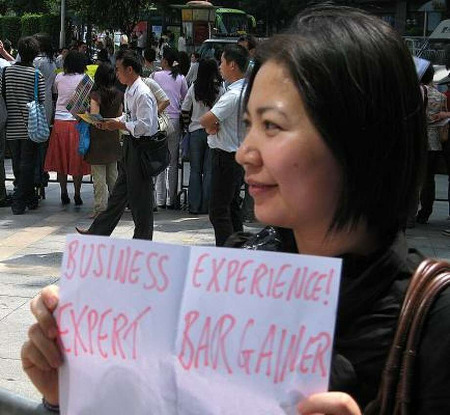 April Wen, holding a sign that extols her expertise as a negotiator on business matters, stands outside a Chinese trade show trying to pick up interpreting work. More Chinese are focusing on careers instead of keeping up with the Communist Party. Photo: BILL FOREMAN, ASSOCIATED PRESS