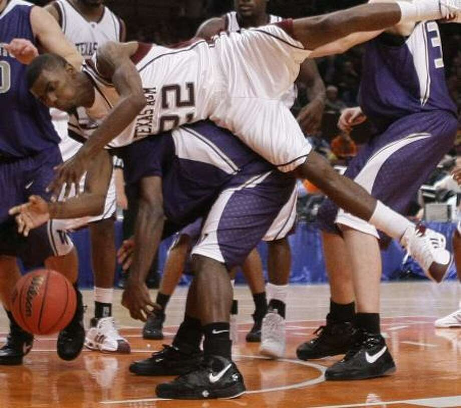 A&M's Dominique Kirk falls over Washington's Justin Dentmon while pursuing a rebound. Photo: JULIE JACOBSON, ASSOCIATED PRESS