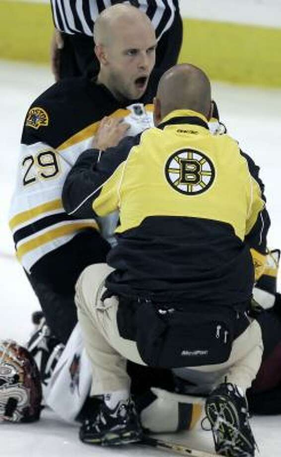 Bruins goalie Alex Auld is attended to after getting kicked in the jaw in the third period. Auld remained in the game. Photo: GENE J. PUSKAR, AP