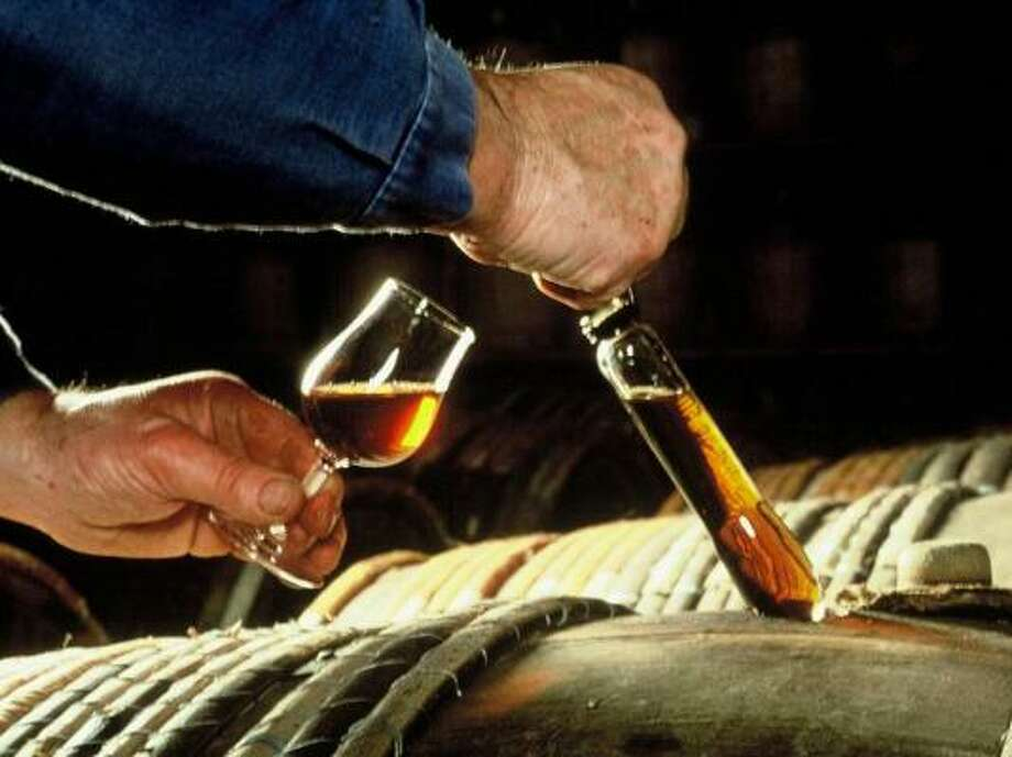 """Dominic Park takes a sample of one of his cognacs using a glass wine """"thief."""" The cognac is going into a small, tulip-shaped glass rather than a large brandy snifter. Photo: COGNAC PARK"""