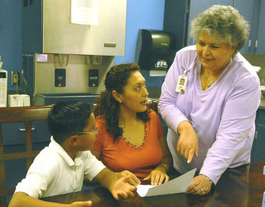 Deaf Smith Elementary social worker Gloria Garcia, right, talks to Maria Zamorano about the academic progress of Maria's son Issac, 7, a second grader. Mrs. Zamorano is also a mentor in Ms. Garcia parenting class. Photo: Ernie Chan, For The Chronicle