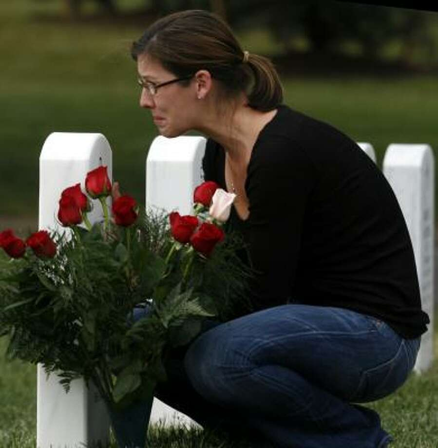 Mary Duffman places flowers at her husband's grave at Arlington National Cemetery in Arlington, Va.; his grave is in Section 60 of the cemetery, where the graves of 335 other men and women killed in Iraq and Afghanistan also lie. Photo: Michel DU CILLE, Washington Post