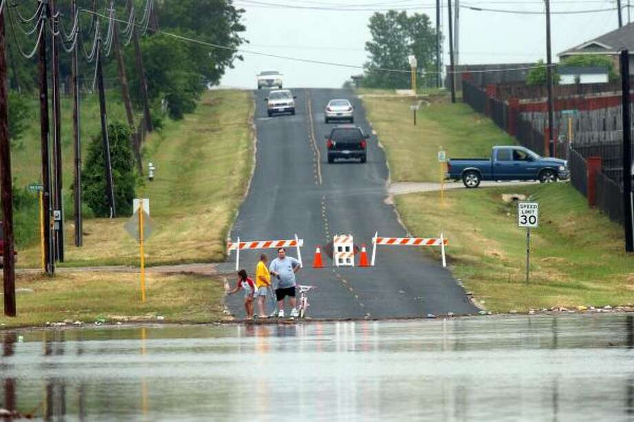 Residents watch as floodwaters flow near their neighborhood in Killeen on Friday. Two days of heavy storms and flooding killed five people in Central Texas. Photo: Steve Traynor, AP