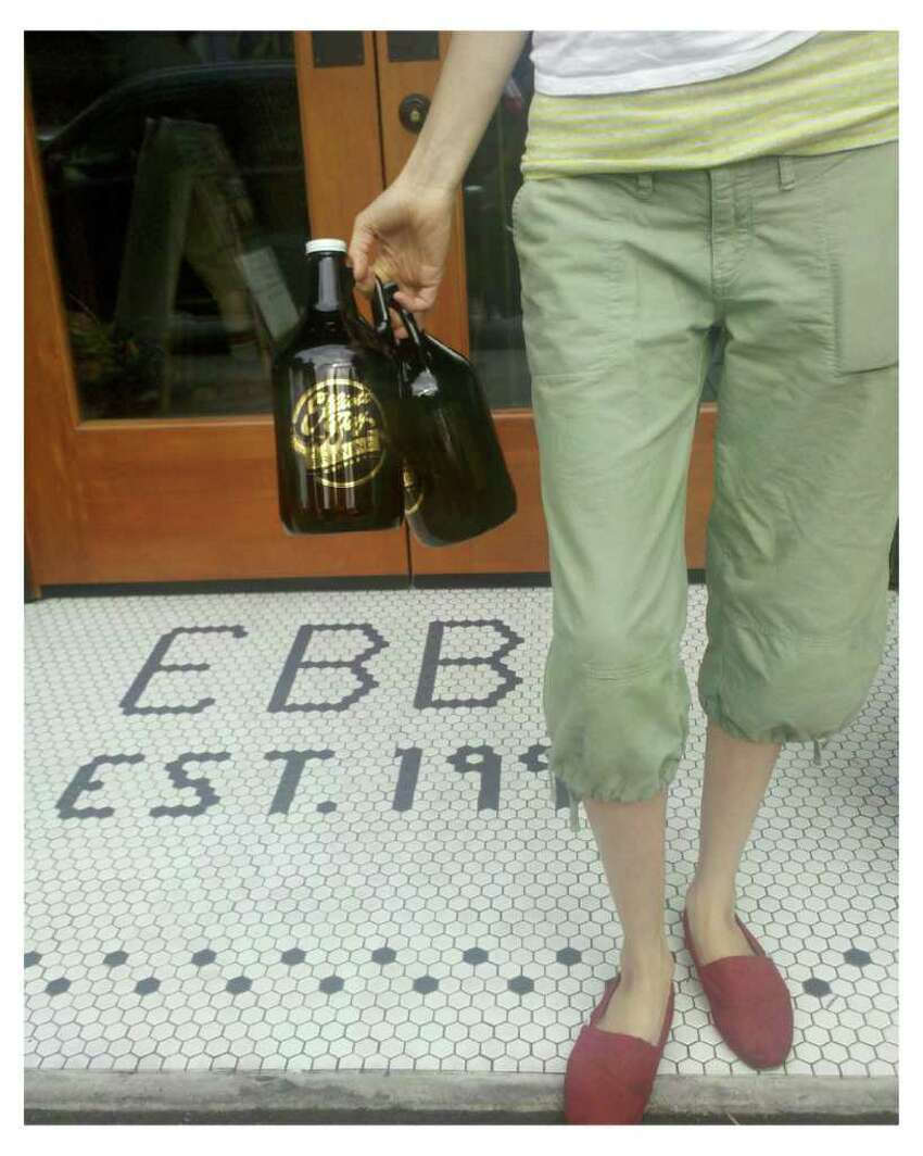 A woman holds beer growlers near the entrance of Elliott Bay Brewery in West Seattle on Tuesday, Aug. 9, 2011.