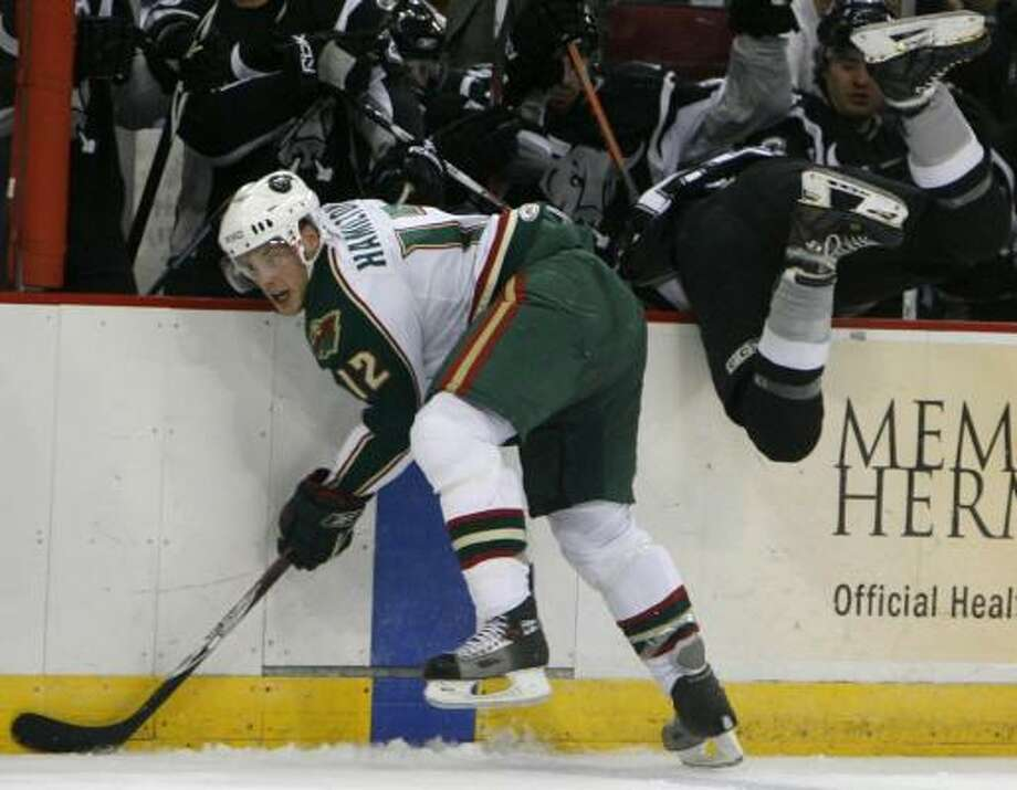 Ryan Hamilton, left, goes after the puck as the Rampage's Logan Stephenson  falls into