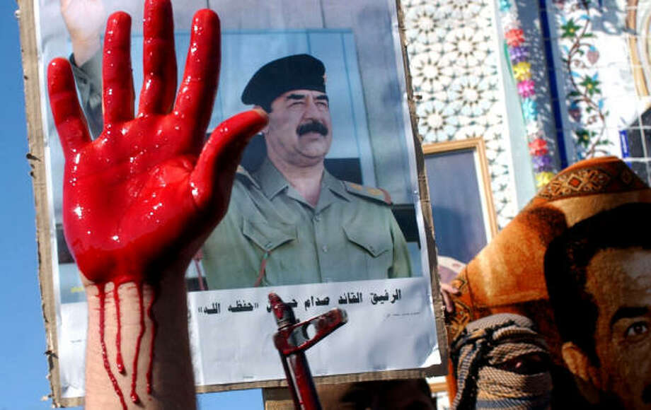 An Iraqi holds out a hand covered with sheep's blood while protesters carry posters of former Iraqi President Saddam Hussein in Dor, north of Baghdad, on Monday. More than 1,000 protesters, some of them armed, marched to express anger over the execution of the ousted Iraqi dictator. Photo: HAMEED RASHEED, AP