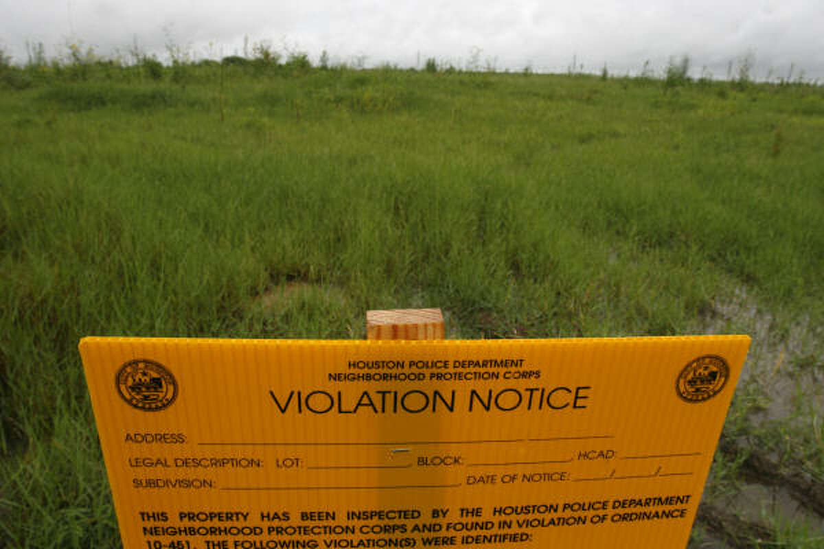 """A Houston Police Department Neighborhood Protection Corps violation notice sits on the vacant lot. The notice said the owners are in violation of the """"neighborhood nuisances"""" article in the city's Code of Ordinances."""