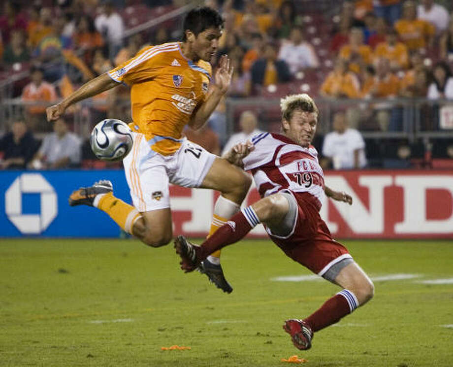 Brian Ching (25) challenges FC Dallas' Bobby Rhine (19) for a ball at Robertson Stadium. Photo: Smiley N. Pool, Chronicle