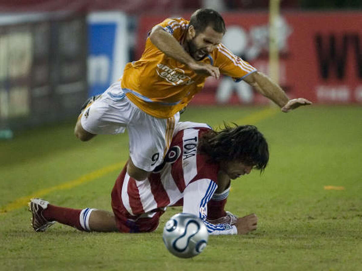 Houston's Brian Mullan (9) tumbles over FC Dallas' Juan Toja (8) in the first half of MLS soccer playoff action at Robertson Stadium.