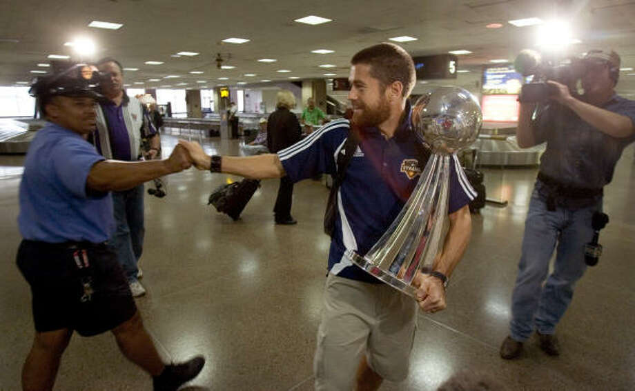 Houston Dynamo team captain Wade Barrett shakes hands with Mhaeed Najeebe after the Dynamo players arrived today at George Bush Intercontinental Airport after winning their second consecutive MLS Cup championship. Photo: Brett Coomer, Chronicle
