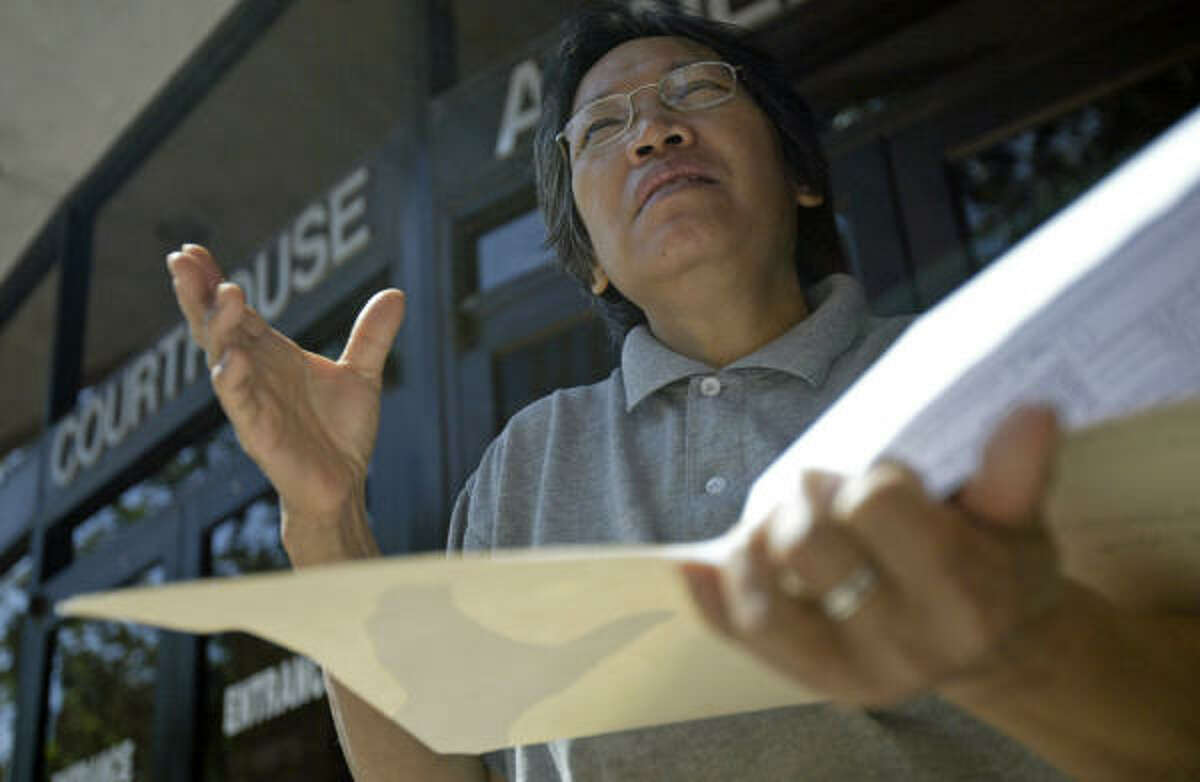 Thuong Tran looks through citations from the city of Houston over a shotgun-style home in the historic Fourth Ward that she has rented to Pearl Franklin, 83, for two years. Tran, whose family owns the Victor houses, said she wants to lease the houses and the property to a nonprofit group that will repair the homes.
