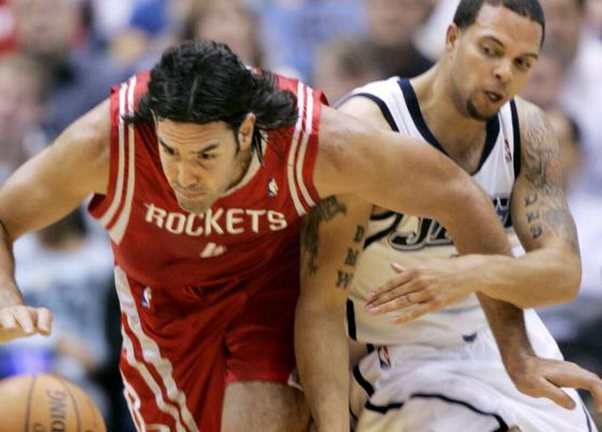 Rockets forward Luis Scola, who scored seven points and grabbed nine rebounds, battles Jazz guard Deron Williams for a loose ball.
