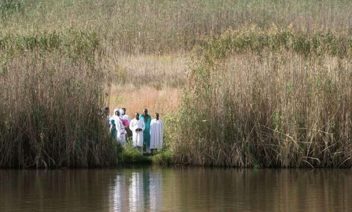 Candidates for baptism by leaders of the Edumisweni church gather at the Emmarentia Dam in Johannesburg.