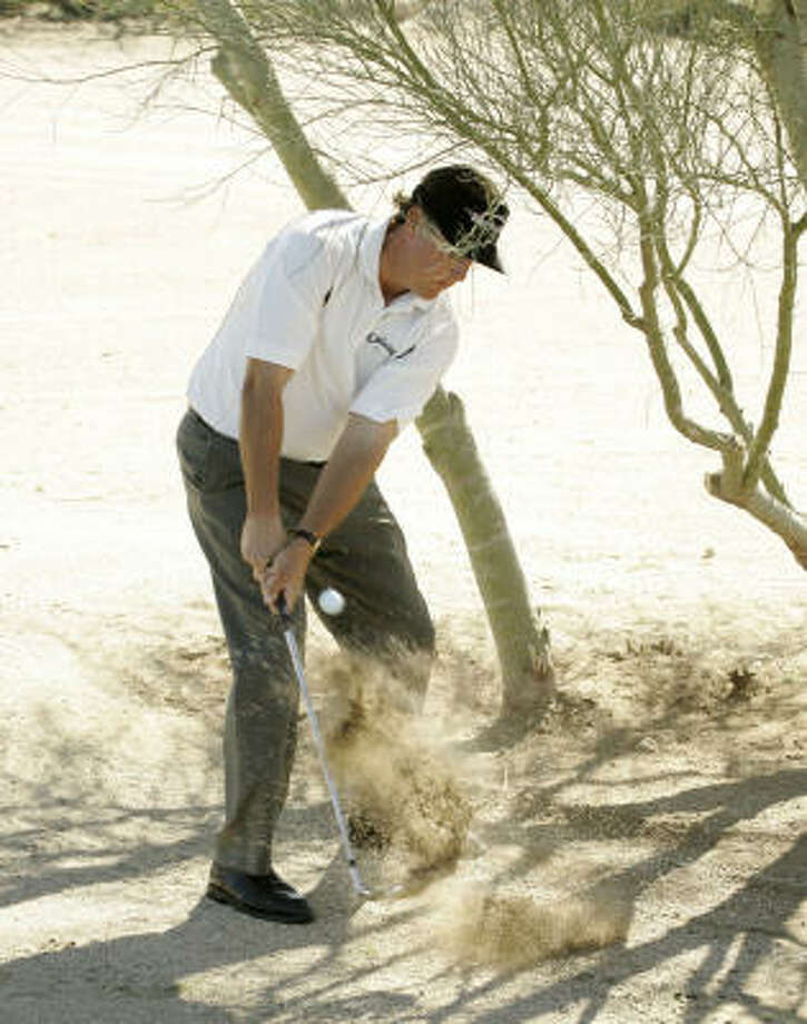 Phil Mickelson gouges his ball from the desert sand under a pala verde tree on the first hole of his second-round match against Justin Rose at the Accenture Match Play Championship in Marana, Ariz. Mickelson lost to Justin Rose 3 and 1. Photo: Matt York, AP