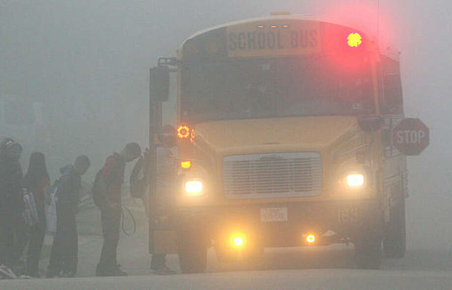Children in the Pearland ISD board a bus this morning in dense fog. Weather today is expected to have areas of dense fog with visibility one quarter mile or less at times early in the morning, and cloudy early in the morning, then becoming partly cloudy. Photo: Mayra Beltran, Chronicle