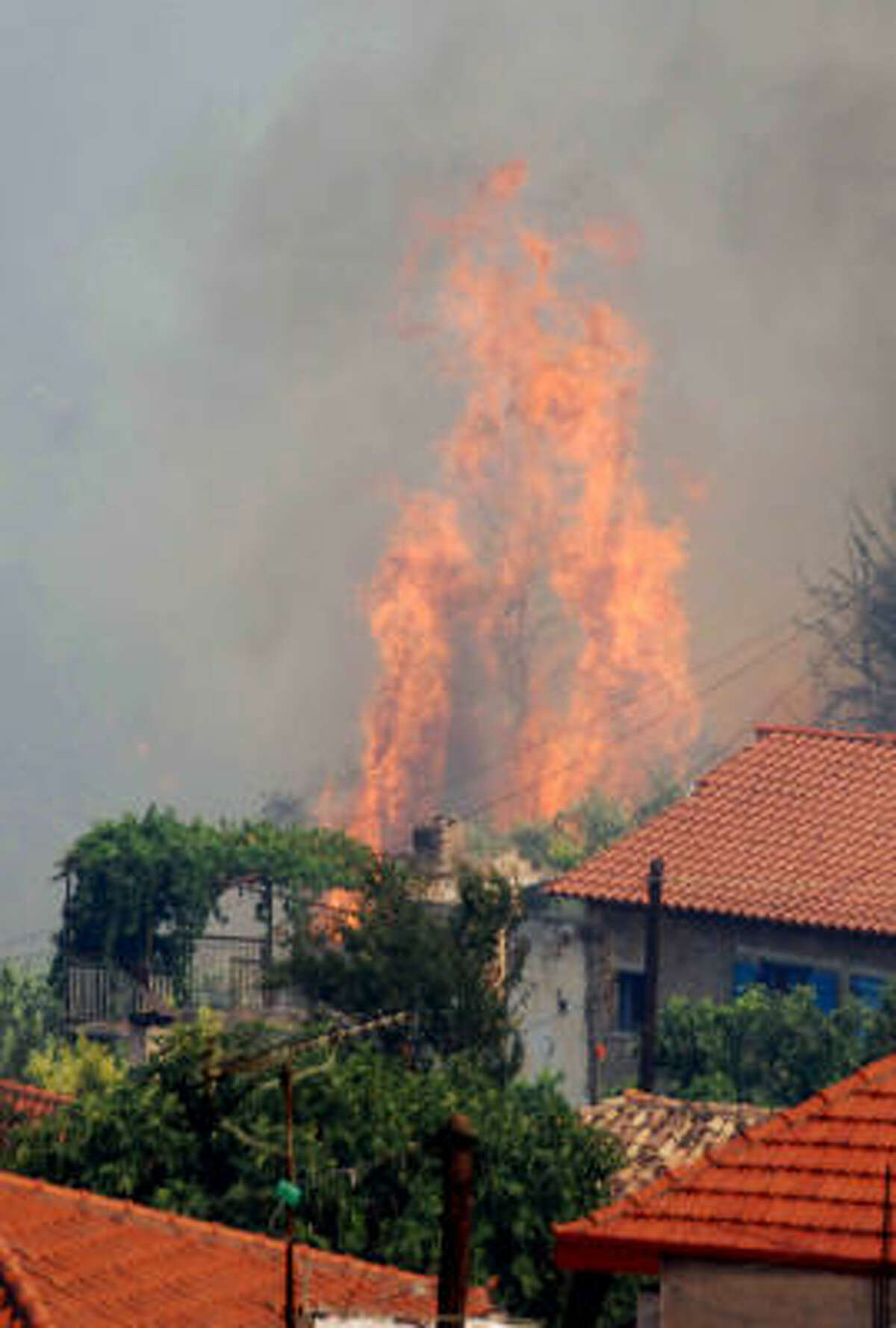 A fire burns next to houses in the village of Mavriki in southern Greece on Wednesday.