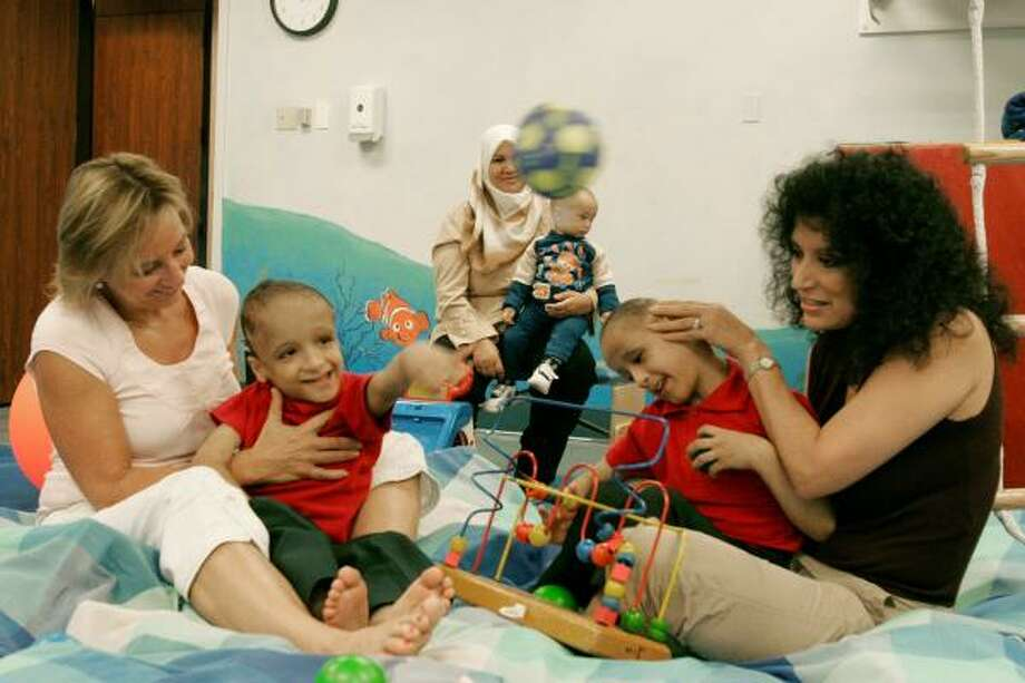 Mohamed Ibrahim, left, throws a ball while sitting with physical therapist Sally Fryer, far left. His twin brother, Ahmed Ibrahim, right works with craniosacral therapist Luci Salyer, far right, in Dallas.  Now 6 years old, the Egyptian twins born joined at the tops of their heads arrived in Dallas last week from their home in Egypt. The boys are walking on their own and speaking both Arabic and English. Photo: Ron Heflin, AP