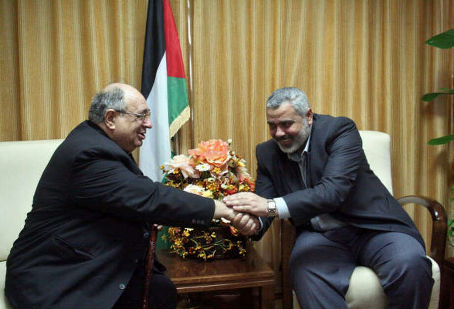 Deposed Palestinian Prime Minister Ismail Haniyeh, right, meets Tuesday with Gaza-based Father Manuel Musalam in Gaza City. The ransacking of Gaza's Catholic convent and an adjacent Rosary Sisters school during Hamas' recent sweep to power broke more than wood and plaster: it signaled the end of a relatively peaceful, even if sometimes uneasy relationship between Gaza's 1.4 million Muslims and 3,500 Christians. Photo: MOHAMMED ALOSTAZ, AP