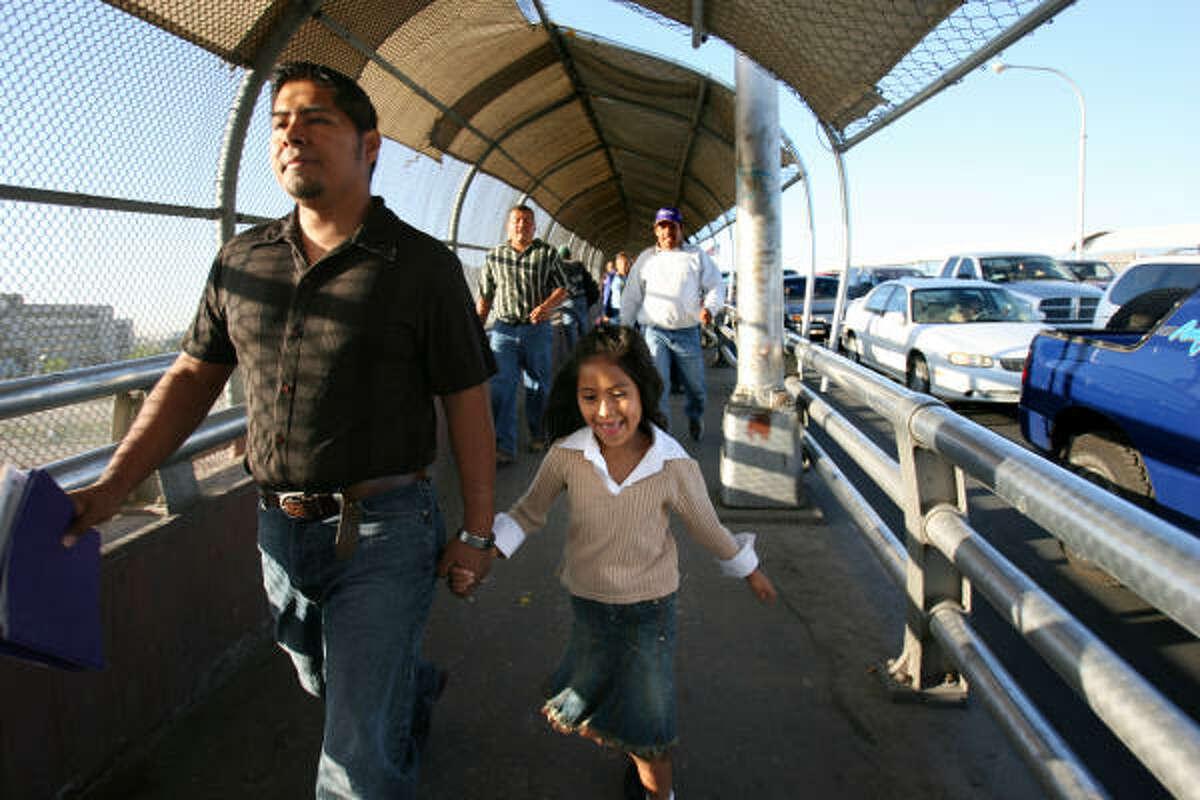 Aaron Ortiz walks his daughter Rachel, 6, across the border from their home in Juarez to her El Paso school each morning.