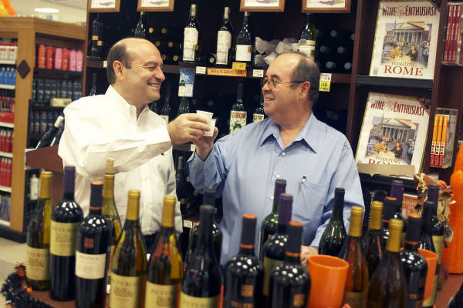 Micky, left, and Roberto Fleischer, founders of Fleischer International Trading, promote their imported Chilean wine at the Kroger on Westpark and Buffalo Speedway. The weakened dollar has hurt Chilean exporters, who must take the losses in order to compete in the U.S. market. Photo: Gabriella Nissen, For The Chronicle