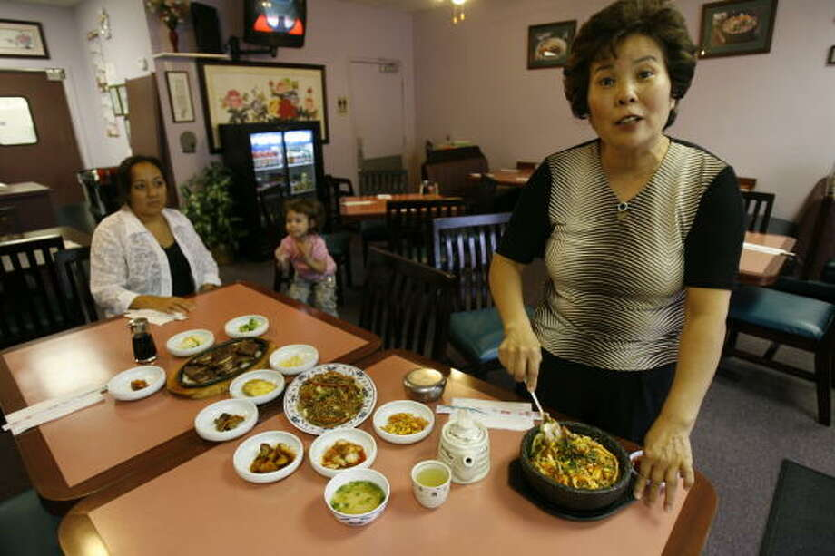 Owner Mia Velez mixes chili paste into a dish of bi bim bap in a hot stone bowl at Korean BBQ. With her are her daughter, Flora Velez, left, and granddaughter, Melea Simpson, 3. Photo: Melissa Phillip, Chronicle