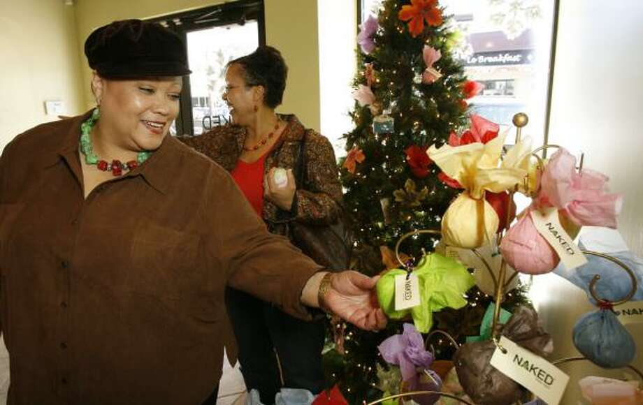 Kimberly Pullam, left, of Corpus Christi, and her sister, Tandra Simcox, of Pearland, shop amid Christmas decorations at Naked Body + Bath in Rice Village last week. Photo: KEVIN FUJII, CHRONICLE