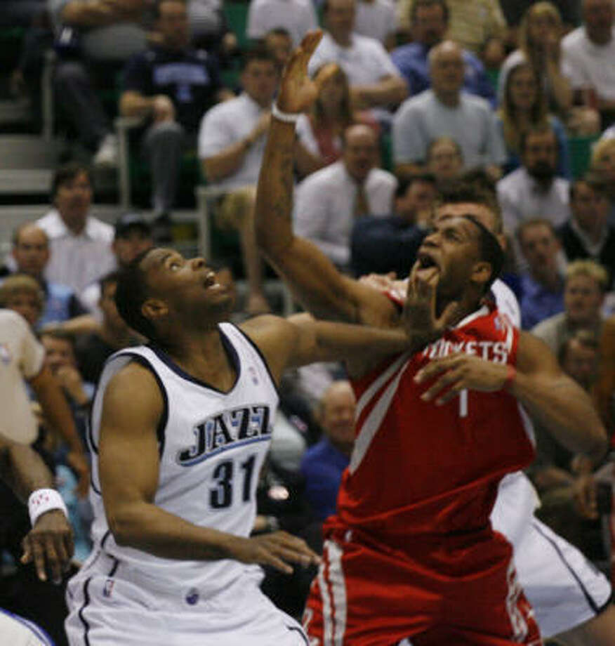 The Jazz count-punched effectively in their first home game of the series, with Jarron Collins, left, supplying rough treatment for Tracy McGrady. Photo: James Nielsen, Chronicle