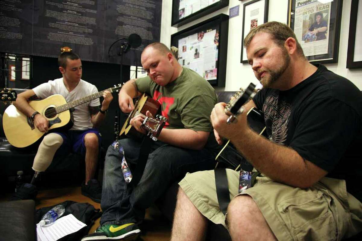 Senior Airman Jeremy Burns (from right) teaches Specialist Bryant Kryck and Specialist Derek Cork guitar chords during Operation Harmony at the Soldiers' Angels Support Center on July 15, 2011. Operation Harmony meets once a week to give soldiers and wounded warriors the opportunity to learn how to play a variety of instruments.