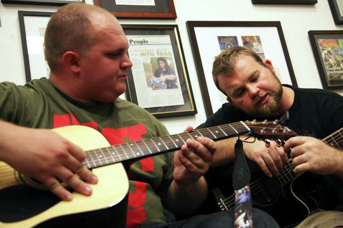Senior Airman Jeremy Burns, right, helps Specialist Bryant Kryck tune his guitar during Operation Harmony at the Soldiers' Angels Support Center on July 15, 2011. Operation Harmony meets once a week to give soldiers and wounded warriors the opportunity to learn how to play a variety of instruments.