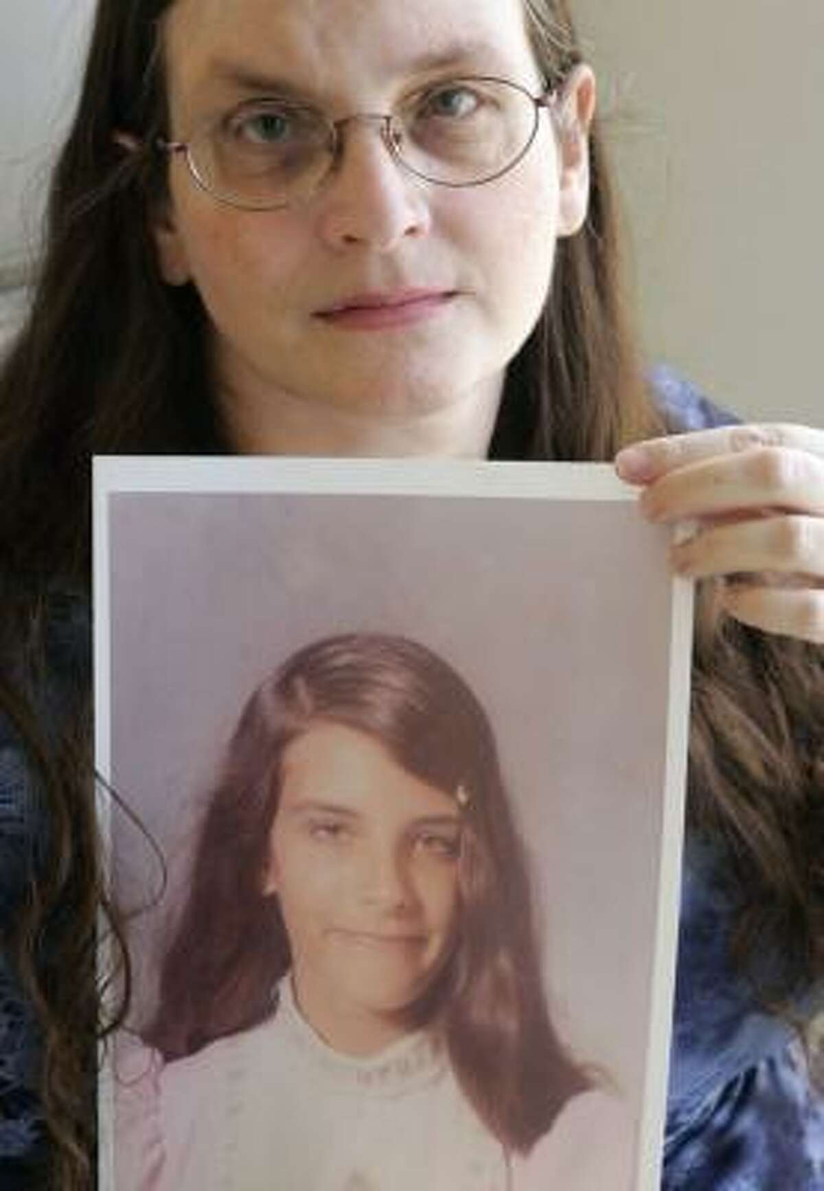 Debbie Vasquez, holding a photo of herself at 14, is suing the Rev. Dale