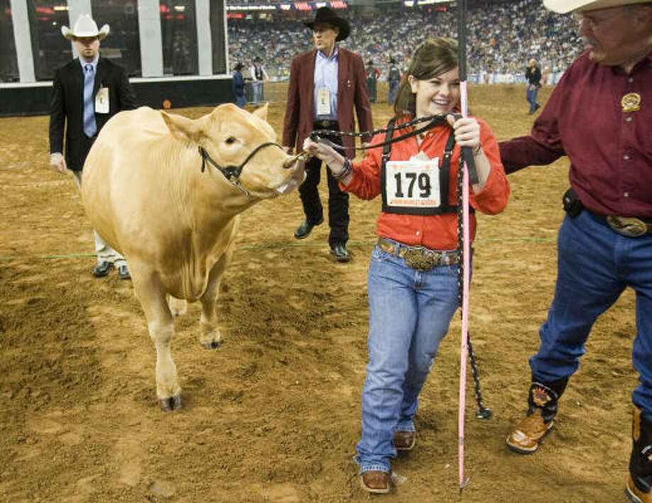 Mackenzi Lea Dorsey, of Seymour, is congratulated by announcer Bill Bailey, right, after her Maine-Anjou was selected by judge Kevin Jensen as the Grand Champion Junior Market Steer at the Houston Livestock Show and Rodeo Friday. Photo: SMILEY N. POOL, CHRONICLE