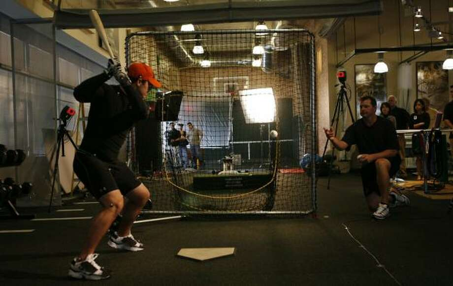 Roger Clemens, right, tosses a ball to son Koby during a swing-analysis exercise at the Roger Clemens Institute for Sports Medicine and Human Performance. Photo: KEVIN FUJII, CHRONICLE