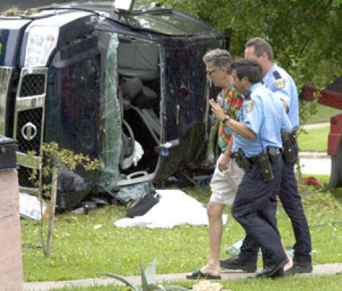 Leo Rudd is escorted from the crash scene of the police chase accident that left his daughter, Rikki Sanchez, dead on Tuesday in Houston.