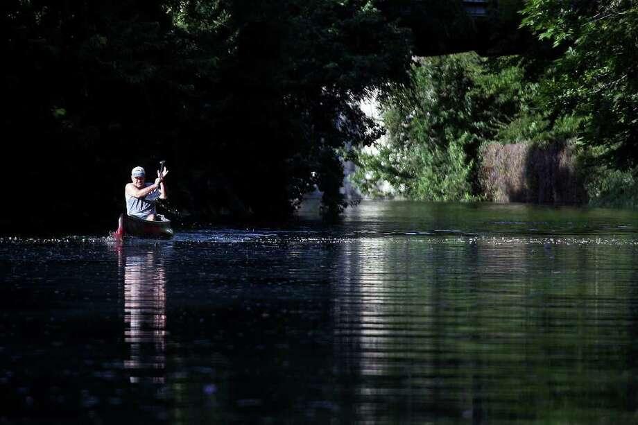 Gib Hafernick paddles his racing canoe on the San Antonio River on Tuesday, August 9, 2011. Photo: LISA KRANTZ, Express-News / SAN ANTONIO EXPRESS-NEWS