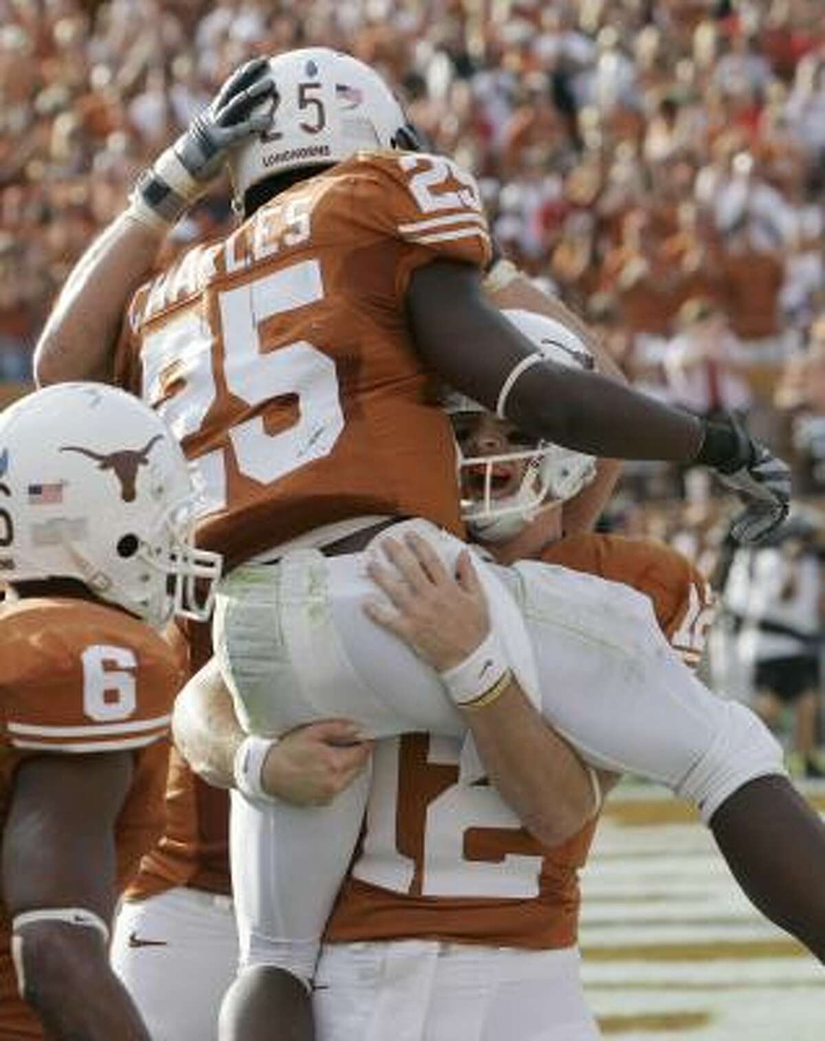 Texas running back Jamaal Charles (25) leaps in the arms of quarterback Colt McCoy (12) after he scored a touchdown.