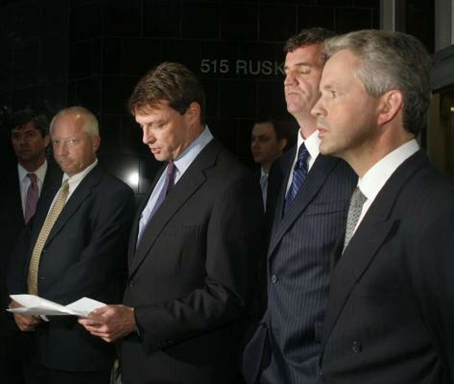 Reid Figel, center left, attorney for former British banker Gary Mulgrew, reads a statement on behalf of Mulgrew, center, Giles Darby, left, and David Bermingham outside federal court downtown on Wednesday. The three pleaded guilty to fraud for their roles in a scheme with former Enron CFO Andrew Fastow. Photo: STEVE UECKERT, CHRONICLE