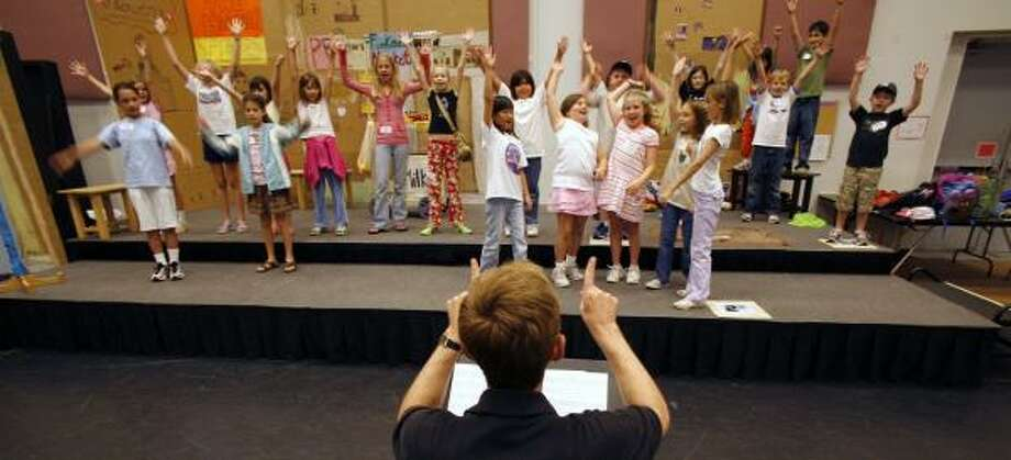 Conductor Gary Gibbs gives opera camp students direction during a rehearsal of The Power of Words. Photo: STEVE UECKERT, CHRONICLE