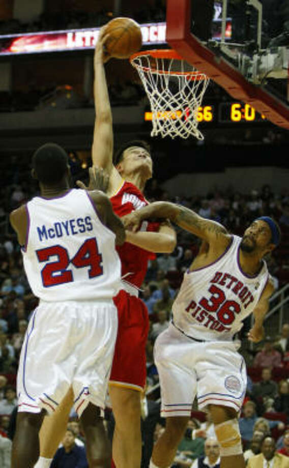 Rockets center Yao Ming, center, is fouled by Pistons center Rasheed Wallace (36) as he goes up for a dunk between Wallace and Antonio McDyess (24) in the second half. Photo: Brett Coomer, Chronicle